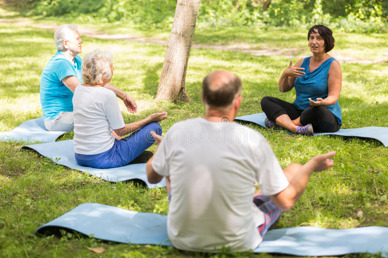 Seniors sitting on exercise mats in a park stock photos