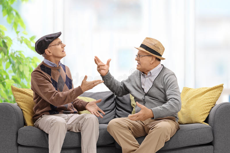 Seniors sitting on a sofa and arguing. With each other stock photography