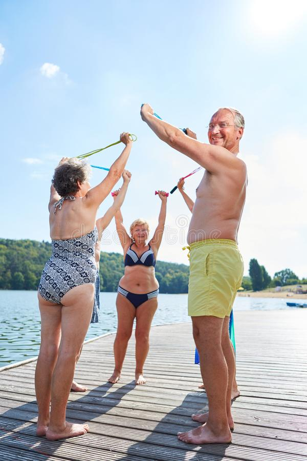 Seniors doing gymnastics on the lake. Seniors with skipping rope do gymnastics together at the lake in summer stock images