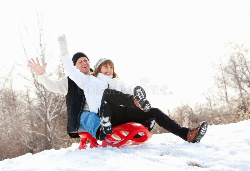 Seniors on sled. Mature couple sledding. Seniors couple on sled in winter park royalty free stock photography