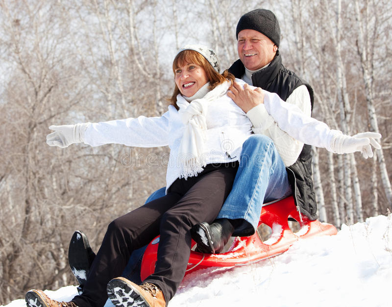 Seniors on sled. Mature couple sledding. Seniors couple on sled in winter park stock photography