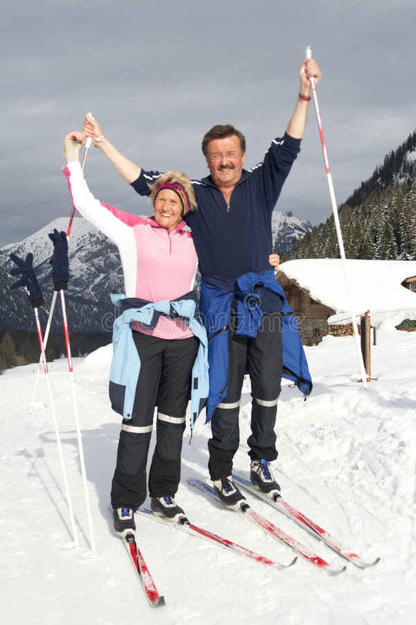 Seniors in the snow. A senior couple outdoor in a winter setting. The active couple is about to go crosscountry skiing royalty free stock image