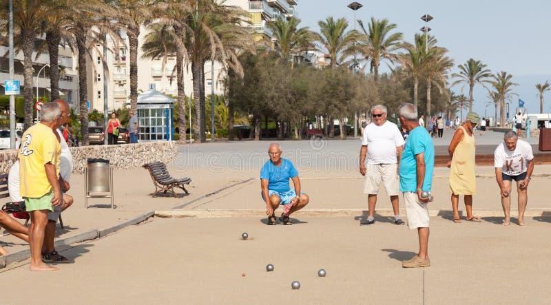 Seniors Spaniards play Bocce on sandy beach royalty free stock photos