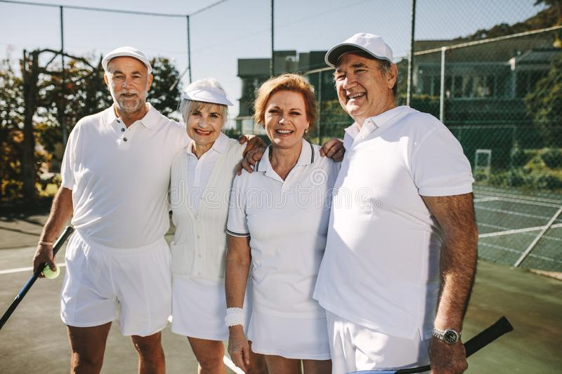 Senior couples in tennis wear standing in a tennis court royalty free stock photo