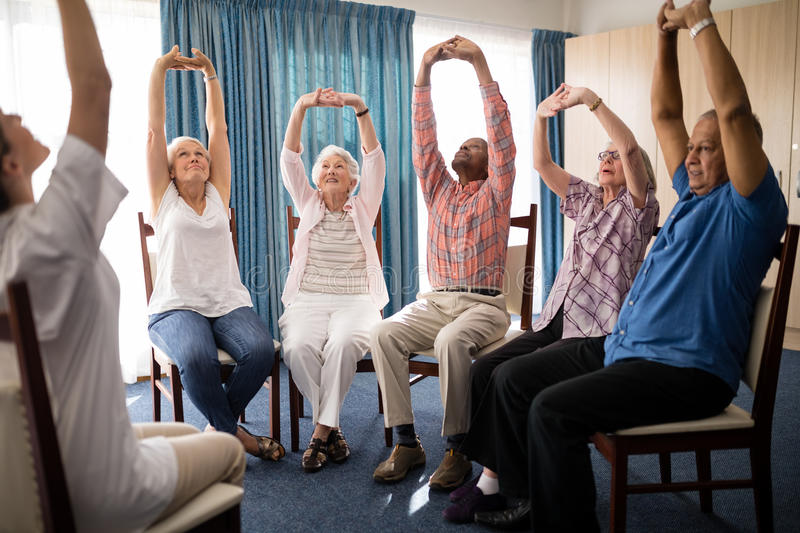 Seniors stretching with female doctor while sitting on chairs. At retirement home royalty free stock photo