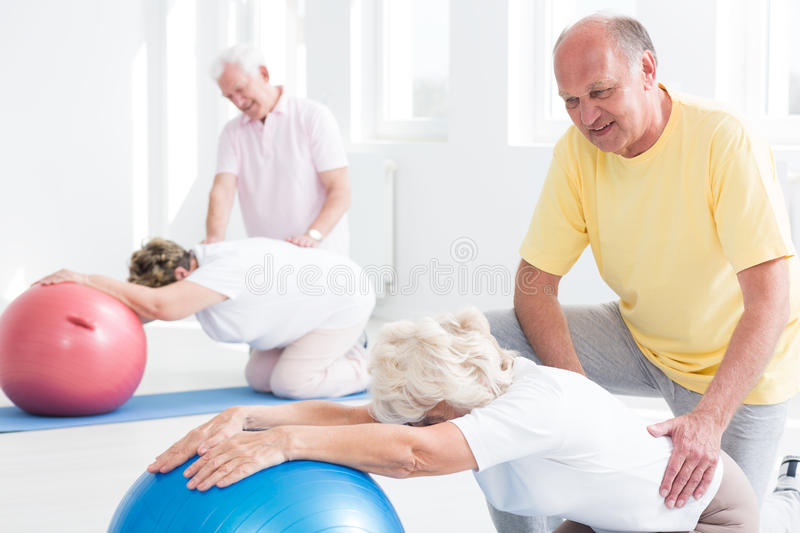 Seniors stretching at the gym. Group of seniors stretching at the gym using exercise balls royalty free stock images