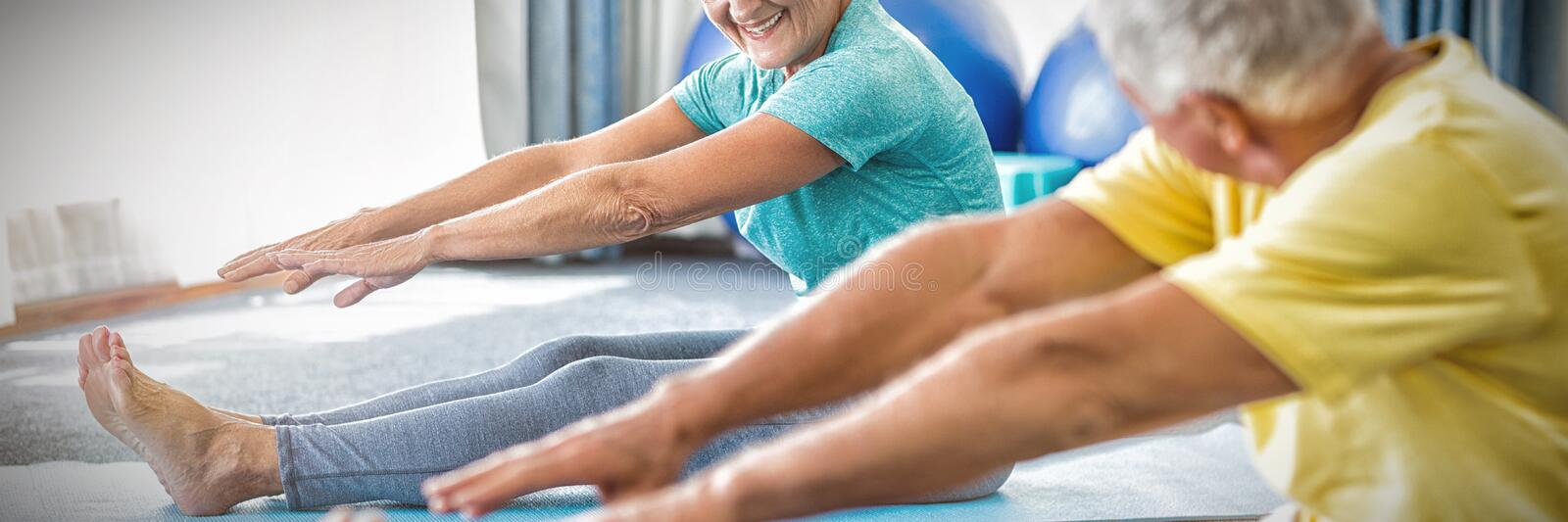 Seniors stretching legs. In studio royalty free stock photography