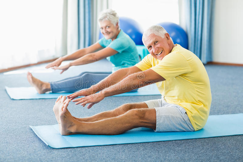 Seniors stretching legs. In a studio stock photography