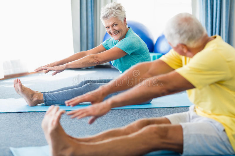 Seniors stretching legs. In a studio stock photos