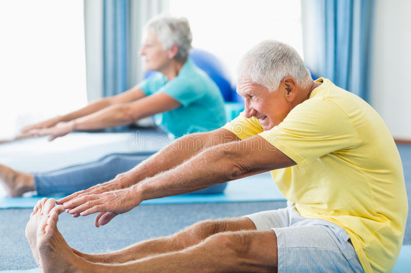 Seniors stretching legs. In a studio royalty free stock photo