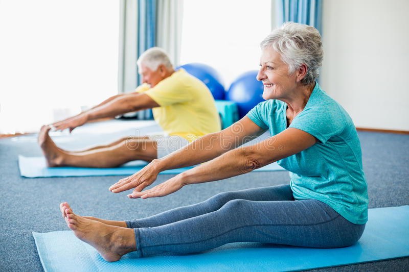 Seniors stretching legs. In a studio royalty free stock photos