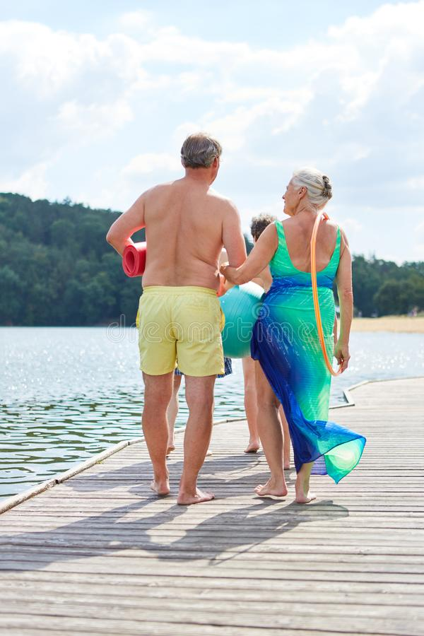 Seniors on summer vacation go swimming. Seniors go swimming together in the summer holiday at the lake or at the weekend stock photo
