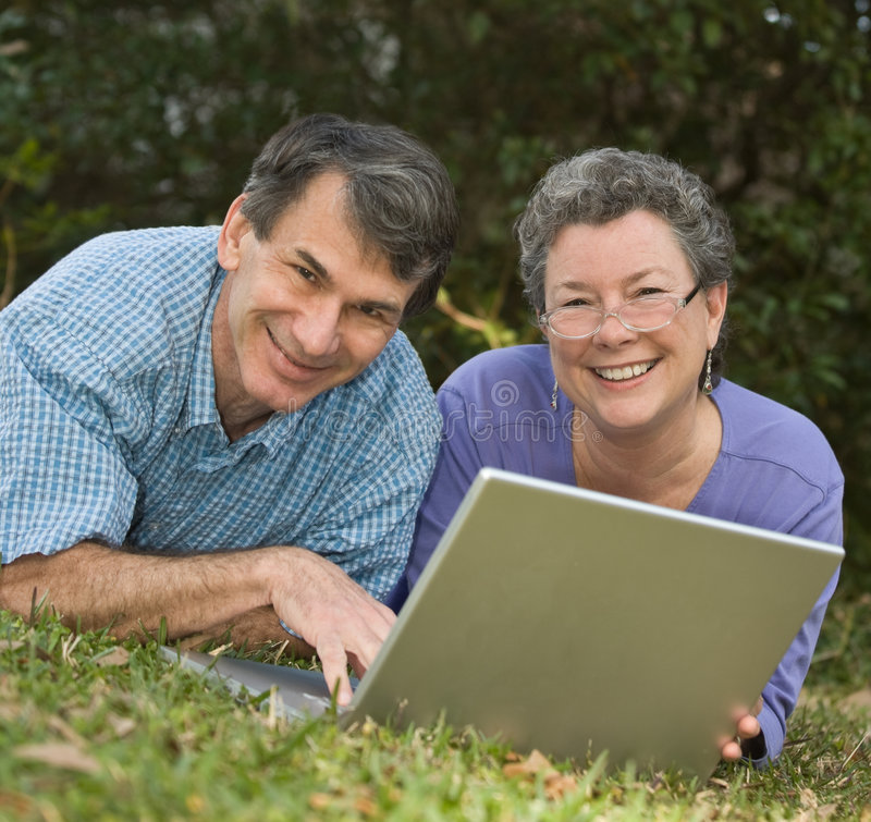 Seniors Surf the Web on Laptop. Happy, cute retired couple lying in the grass working on their laptop in an outdoor setting