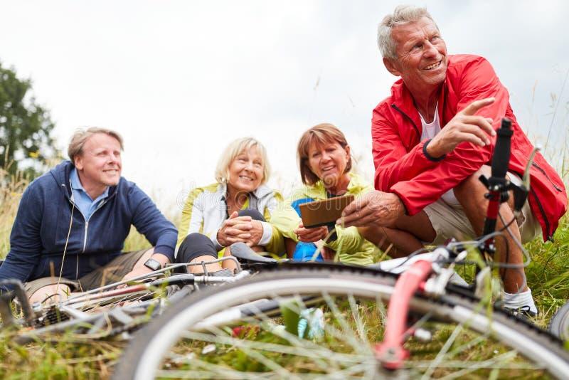 Seniors take a break on a bike tour. Seniors as friends take a break in nature on their bike tour royalty free stock photo