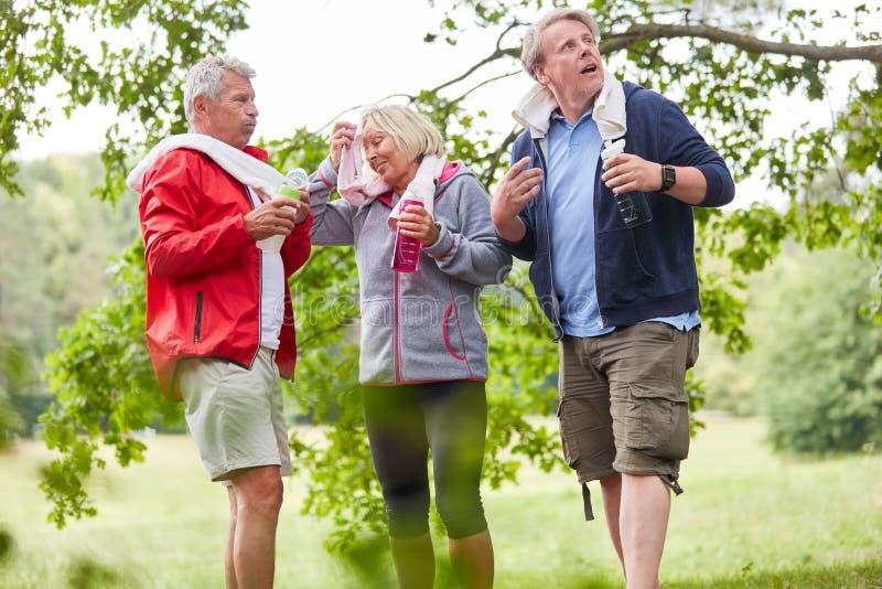 Seniors take a break on the hike. Seniors make a break on the hike exhausted and sweaty stock photography
