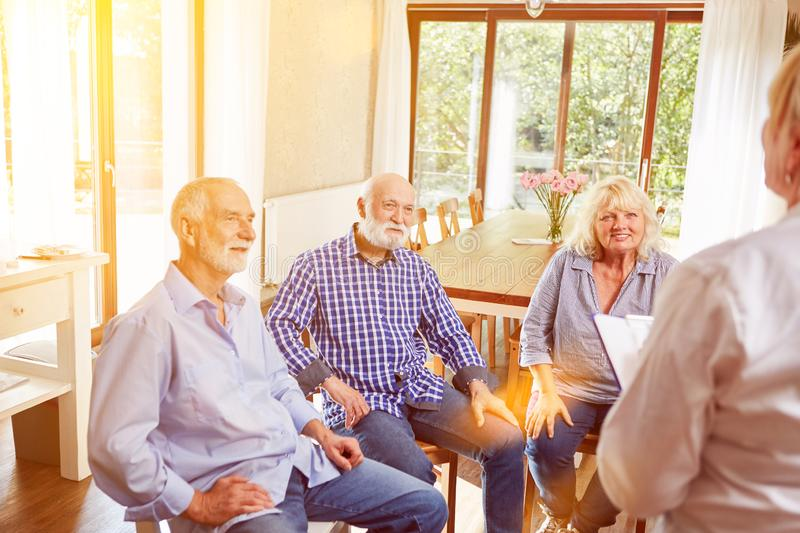 Seniors talk in group psychotherapy. Seniors talking in group psychotherapy with therapist in nursing home royalty free stock image