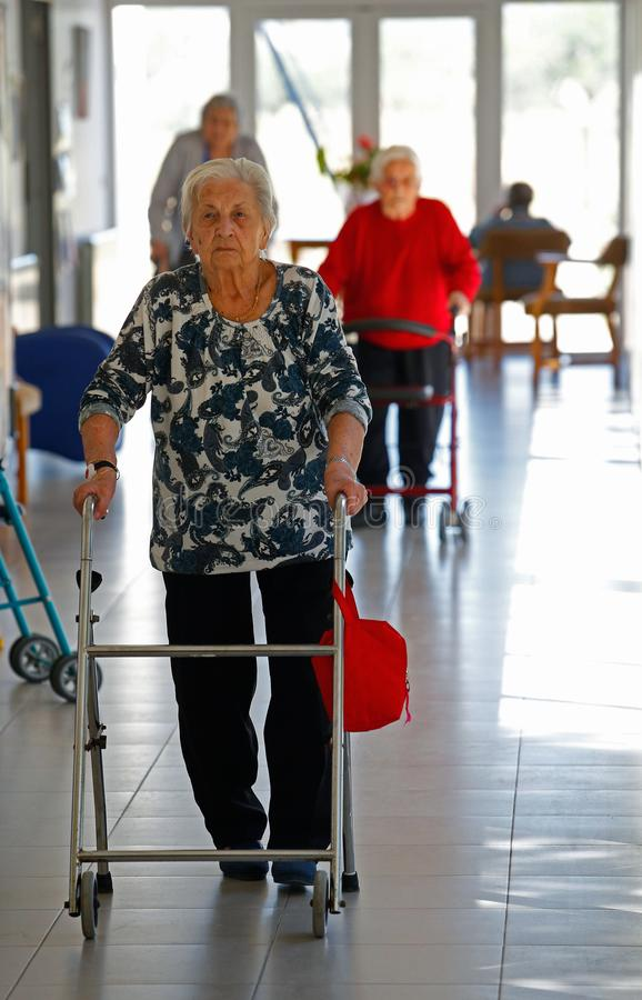 Seniors during their daylife on a nursing home in Mallorca vertical. Seniors walk on the hall of their nursing home in the Spanish island of Mallorca during an royalty free stock photography