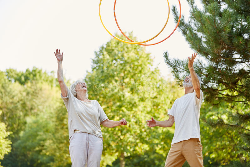 Seniors throwing hula hoops in the air. Happy seniors throwing hula hoops in the air and having fun royalty free stock photography