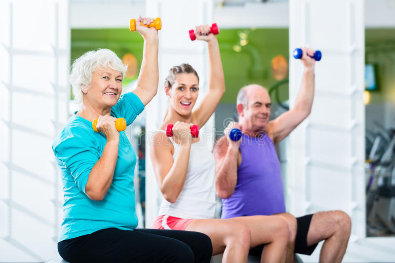 Seniors with trainer in gym at sport lifting barbell royalty free stock photography