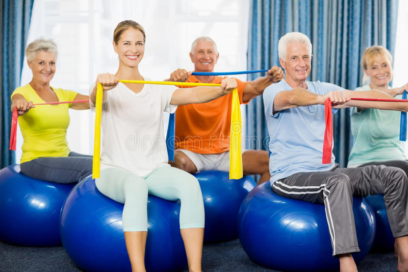 Seniors using exercise ball and stretching bands. During sports class royalty free stock image