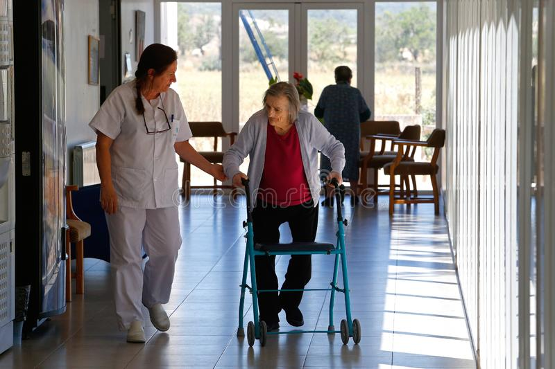 Seniors during their daylife on a nursing home in Mallorca. Seniors walk on the hall of their nursing home in the Spanish island of Mallorca during an open doors royalty free stock photography