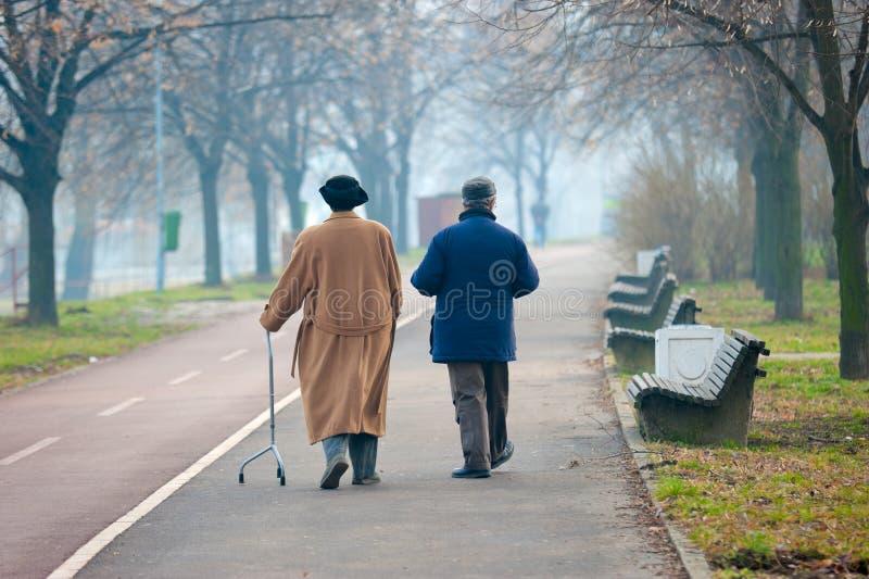 Seniors walking. A couple of seniors walking near a river in winter stock photo