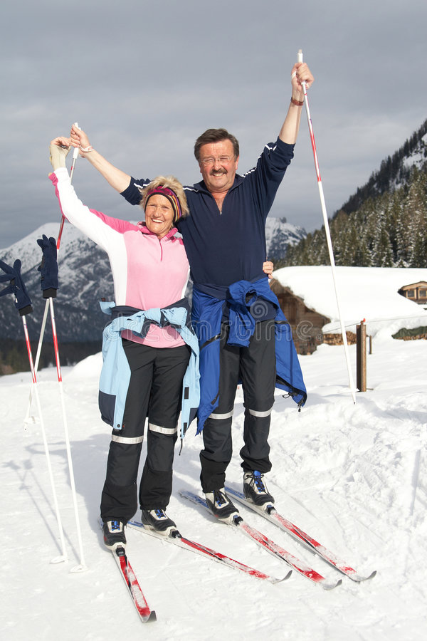 Seniors in winter fun. A senior couple outdoor in a winter setting. The active couple is about to go crosscountry skiing stock photos