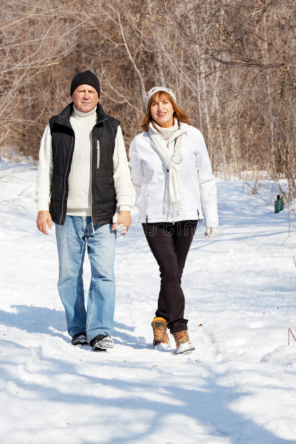 Seniors in winter park. Happy seniors couple in winter park. Elderly mature people royalty free stock images