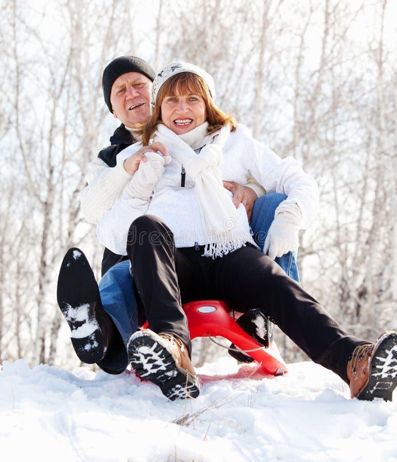 Seniors in winter park. Mature couple sledding. Seniors couple on sled in winter park stock photography