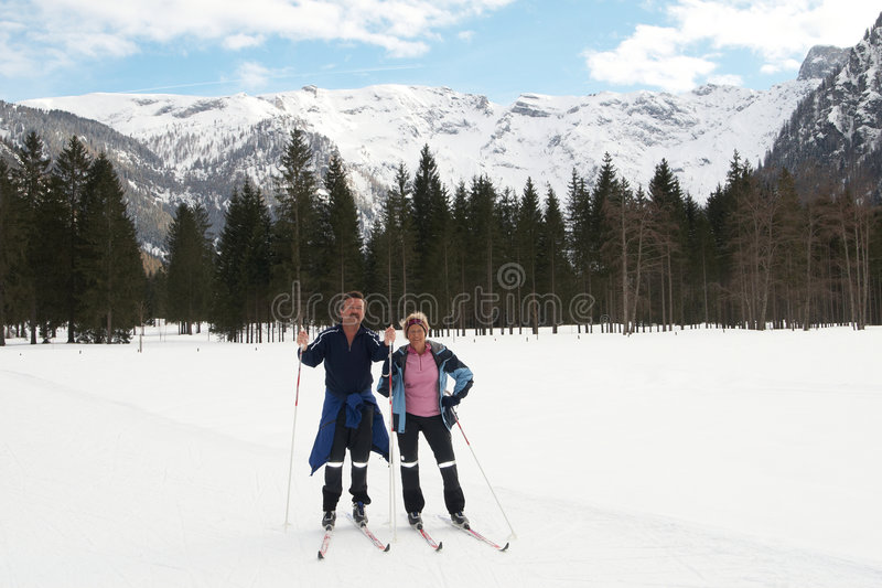 Seniors in winter scene. A senior couple outdoor in a winter setting. The active couple is about to go crosscountry skiing royalty free stock photography