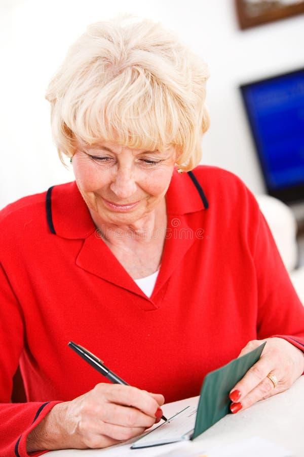 Seniors: Woman Cheerfully Writing Checks royalty free stock image