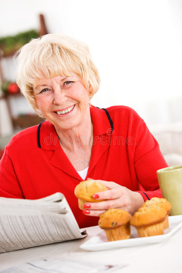 Seniors: Woman Having A Muffin and Newspaper royalty free stock photography