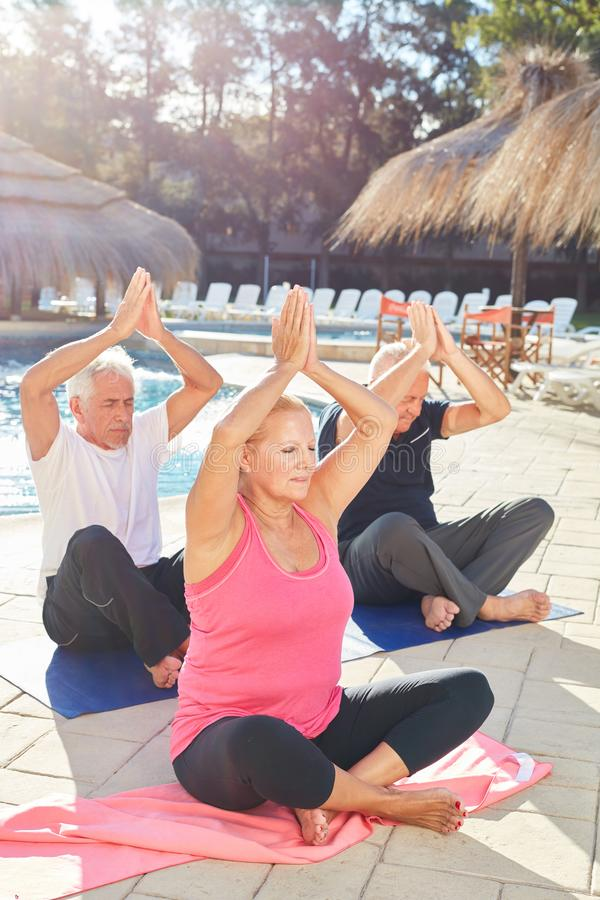 Seniors in the yoga workshop by the pool. Seniors do an exercise in the yoga workshop by the pool at the Wellness Hotel stock photography