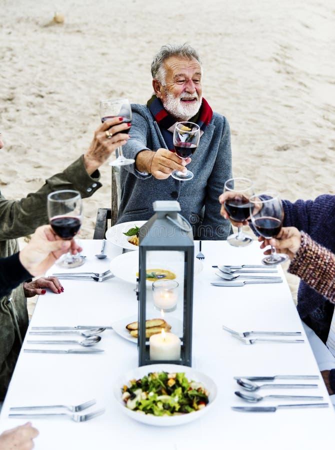 Seniory wznosi toast z czerwonym winem przy plażą obraz royalty free