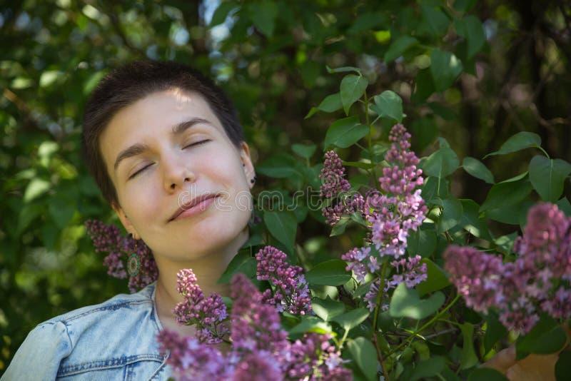 senjoying温暖的天的美丽的逗人喜爱的女孩在淡紫色开花的树下 图库摄影