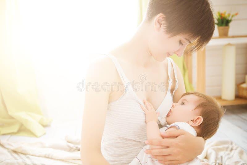 Seno d'alimentazione della giovane madre il suo bambino nella sala immagine stock libera da diritti