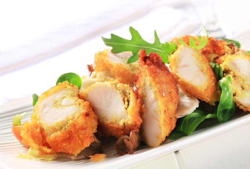 Seno di pollo impanato con i verdi dell'insalata immagine stock