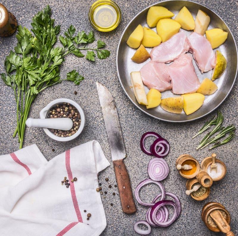 Seno di tacchino crudo con la patata, la pera, la cipolla rossa e le erbe, con vari condimenti, coltello d'annata per carne, sul  immagini stock