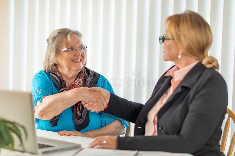Senoir kvinna som skakar händer med affärskvinnan Near Laptop Computer royaltyfri bild