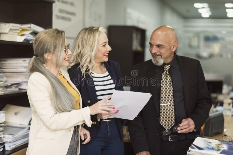 Senor het chef- spreken met twee wijfjeswerknemers op kantoor royalty-vrije stock foto