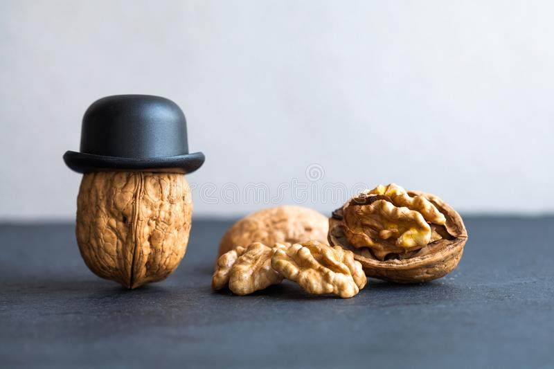 Senor walnut black hats, half nutshell on stone and gray background. Creative food design poster. Macro view selective royalty free stock photos