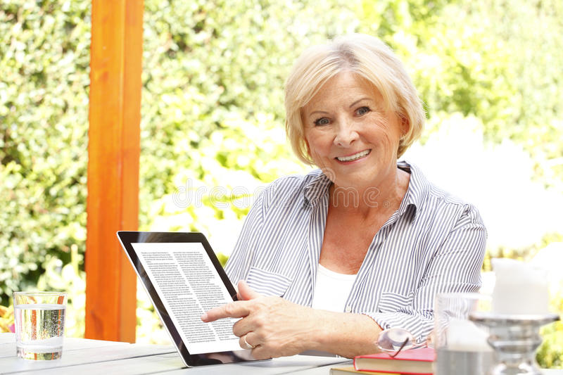 Senor woman with diigital tablet royalty free stock image
