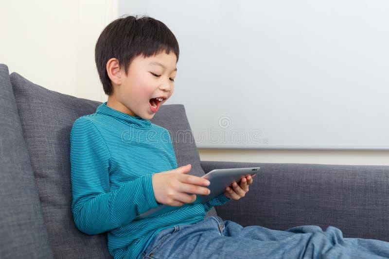 Sensação asiática do rapaz pequeno que excita para usar a tabuleta fotografia de stock royalty free