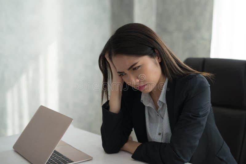 A sensação asiática nova da mulher de negócios forçou/preocupação/dor de cabeça/disappoin imagem de stock