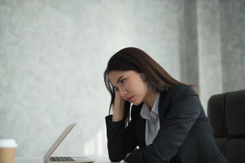A sensação asiática nova da mulher de negócios forçou/preocupação/dor de cabeça/disappoin fotos de stock royalty free