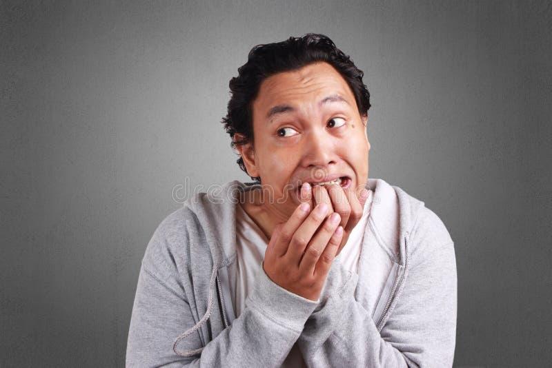 Sensação do homem assustado ao morder seu dedo foto de stock