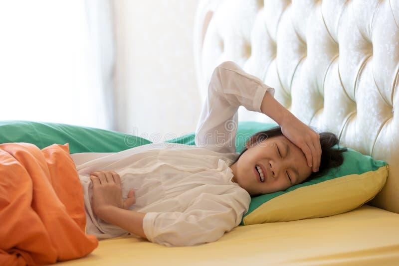 Sensación asiática de la muchacha enferma, femenina teniendo el dolor de estómago, el dolor de cabeza y h imágenes de archivo libres de regalías