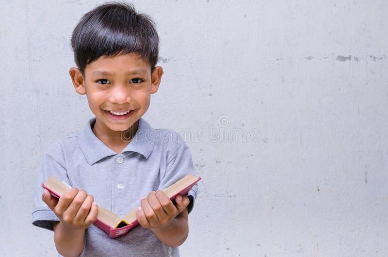 Sensación asiática del niño feliz con un libro fotos de archivo