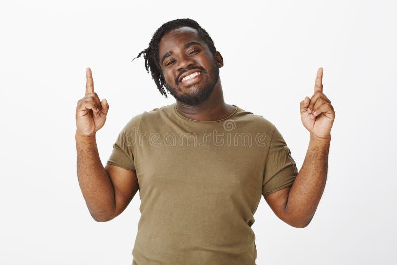 Sensación como ganador Retrato del hombre regordete de piel morena encantador con actitud positiva y feliz, aumentando los dedos  foto de archivo
