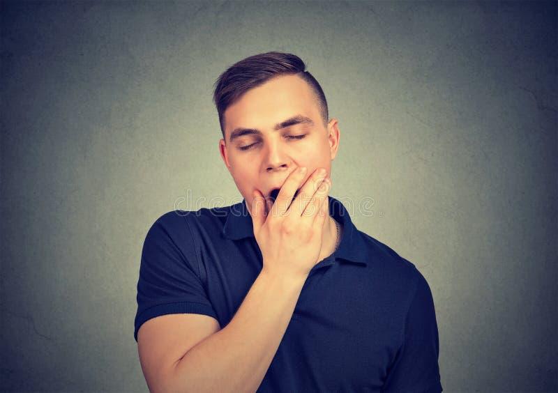 Sensación de bostezo soñolienta del hombre joven cansado imagenes de archivo